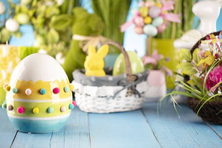 Easter theme. Easter decorations. Easter eggs in basket and cabbage leaf. Bouquet of spring flowers. Blue background. Archivio Fotografico