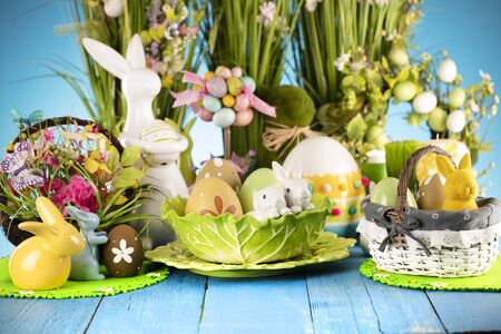 Easter theme. Easter decorations. Easter eggs in basket and cabbage leaf. Bouquet of spring flowers. Blue background.