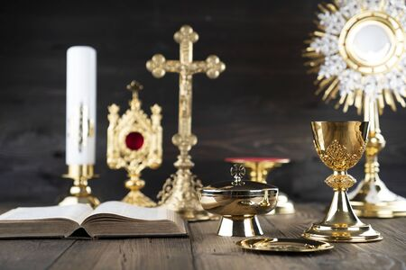 Catholic religion concept. Catholic symbols composition. The Cross, monstrance,  Holy Bible and golden chalice on wooden altar and gray background.