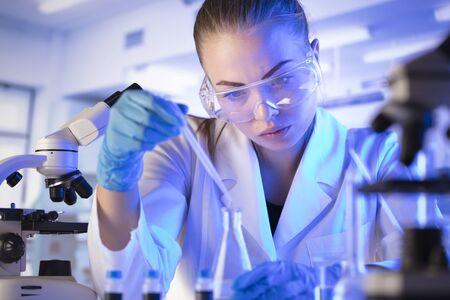 Wissenschaftsforschungskonzept. Junger Wissenschaftler während des Experiments und mit Mikroskop im modernen Labor. Glasröhrchen und Becher.