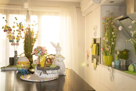 Easter theme. Easter decorations. Easter eggs in basket and easter bunny. Bouquet of spring flowers.