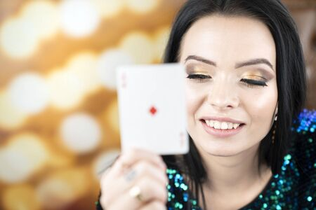 Casino. Portrait of pretty young woman holding playing cadrs in her hand.