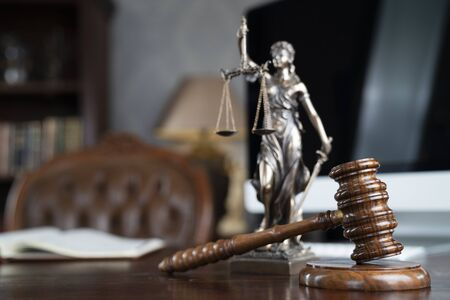 Law theme. Judge chamber. Gavel and Themis statue on brown shining desk. Collection of legal books in the bookshelf. Stock Photo