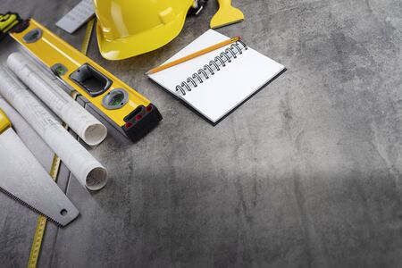 Contractor concept. Tool kit of the contractor: yellow hardhat, libella, hand saw. Plans and notebook on the gray tiles background.