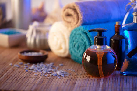 Spa and wellness concept. Bottles with cosmetics, rolled up towels, bath salts and care products on wooden paneling.