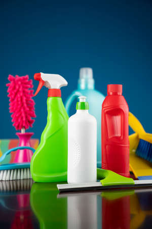 House and office cleaning theme. Colorful cleaning kit on shing brown table and blue background.