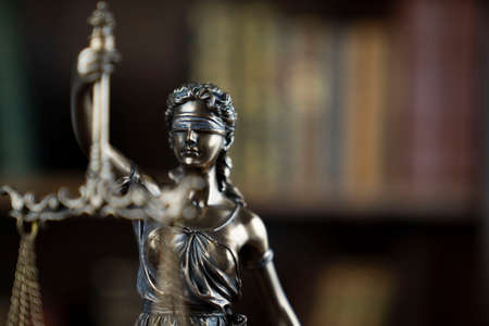 Law theme. Judge chamber. Themis statue on brown shining desk. Collection of legal books in the bookshelf. Stock Photo