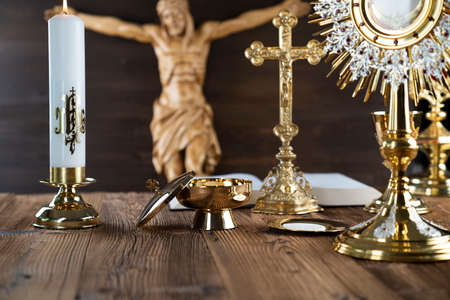 Catholic religion symbols. The Cross, monstrance, Jesus figure, Holy Bible and golden chalice on the rustic wooden altar.