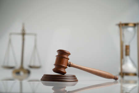 Law and justice concept. Gavel, scale and hourglass on the off-white background.