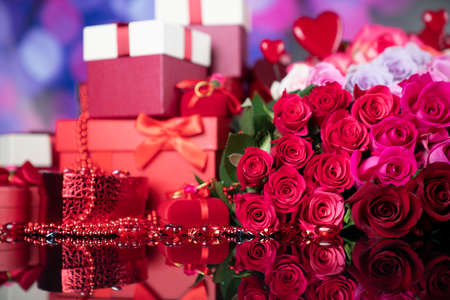 Wedding day concept. Big bouquet of roses and boxes with wedding gifts on glass table. Archivio Fotografico