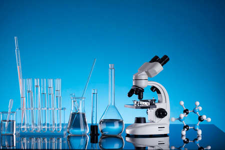 Coronavirus pandemic theme. Science research concerning fast covid tests and anti-covid vaccine. Beakers, microscope and test tubes on blue background.