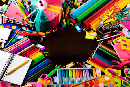 School supplies. Set of colorful school accessories isolated on the brown table. Top view. Archivio Fotografico