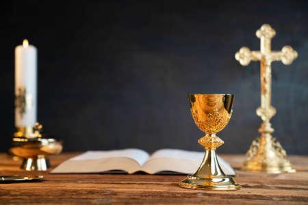 Catholic religion concept. Catholic symbols composition: The Cross, monstrance, Holy Bible and golden chalice.