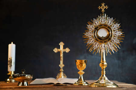 Catholic religion concept. Catholic symbols composition: The Cross, monstrance,  Holy Bible and golden chalice. Stockfoto