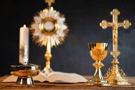 Catholic religion concept. Catholic symbols composition: The Cross, monstrance, Holy Bible and golden chalice. Foto de archivo