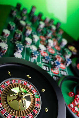 Casino theme, close up of roulette, red and black numbers. Stack of chips in the background.