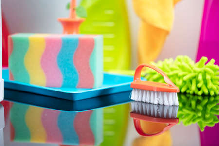 House and office cleaning theme. Colorful cleaning kit on glass table. Standard-Bild