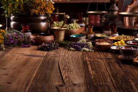 Natural medicine theme. Assorted dry herbs in bowls and brass mortar on rustic wooden table. Stock Photo