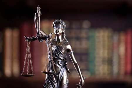 Law and justice concept. Themis sculpture in lawyers office. Bookshelf with legal books in background.