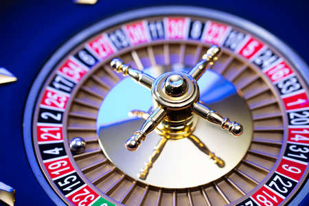 Casino theme, close up of roulette, red and black numbers. Blue background. Standard-Bild