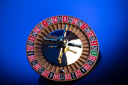 Casino theme, close up of roulette, red and black numbers. Blue background.