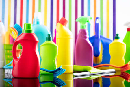 House and office cleaning theme. Colorful set of bottles with clining liquids on background in the form of colorful stripes.