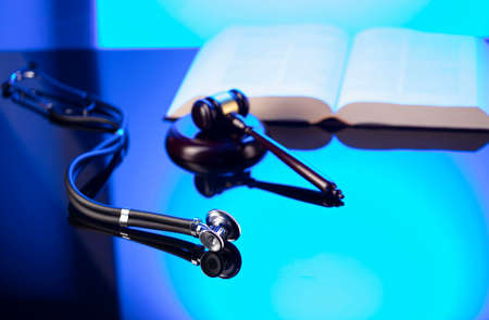 Medical law concept. Gavel, legal code and stethoscope on the glass table. Blue light.