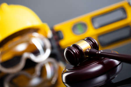 Construction law concept. Helmet and judge's gavel on the gray background.