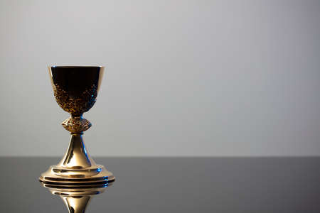 Catholic religion concept background. Golden chalice, place for text.