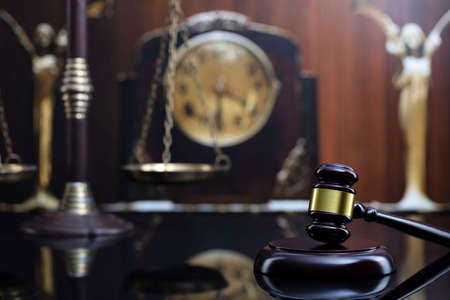 Law concept. Judge wooden gavel, scale and old clock on brown background.