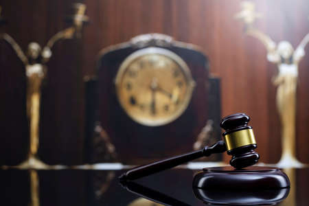 Law concept. Judge wooden gavel and old clock on brown background. 版權商用圖片