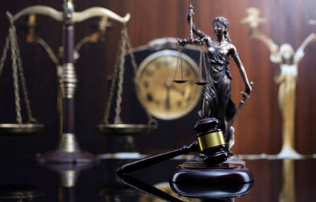 Law concept. Judge wooden gavel, scale, old clock and Themis statue on brown background.