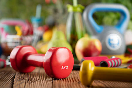 Fitness concept. Healthy nutrition: fruits and vegetables. Equipment for fitness exercises: weighing machine and dumbbells.