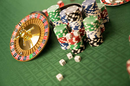 Casino concept.  Roulette wheel, poker chips and dice on green table and on  yellow bokeh background. Reklamní fotografie
