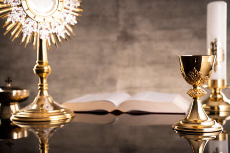 Catholic symbols composition. Religion concept. The Cross, monstrance, Holy Bible and golden chalice gray background.
