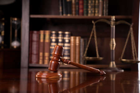 Law theme. Lawyers office. Gavel and scale on the brown desk. Bookshelf with legal books. Stock Photo