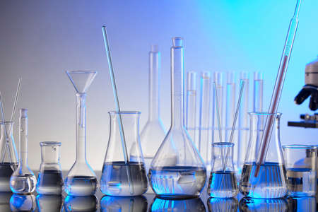 pandemic theme. Science research concerning fast  tests and  vaccine. Microscope, beakers and test tubes on blue background.
