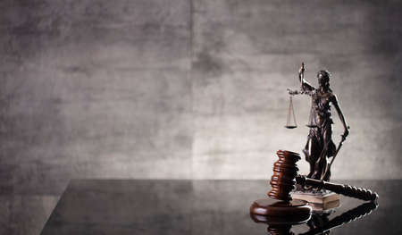 Law and justice concept. Law symbols composition: judge's gavel, Themis  statue and scale. Gray background.