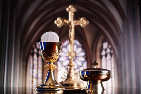 First Holy Communion. Catholic religion theme. Crucifix, the Croass and Golden chalice and wafer on the altar.