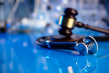 Medical law concept. Gavel and stethoscope on the glass table. Blue light.