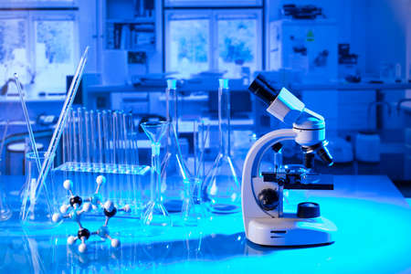 pandemic theme. Science research concerning fast tests and anti-vaccine. Microscope, beakers and test tubes in the scientific laboratory.
