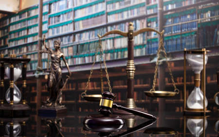 Law and justice concept. Gavel of the jugde, Themis sculpture and scale of justice in the court library.