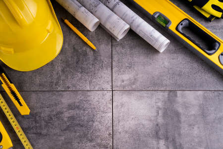Contractor theme. Tool kit of the contractor: yellow hardhat, libella and tools on the gray tiles background. 版權商用圖片
