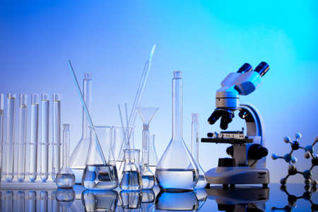 Laboratory investigations. Microscope, glass tubes and beakers on blue background.