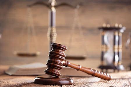 Law theme. Judge chamber. Judge's gavel, scale, Themis sculpture on the brown rustic desk and the brown background.