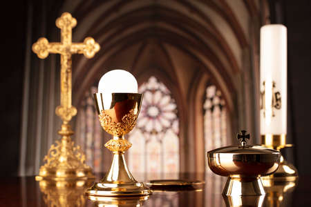 First Holy Communion. Catholic religion theme. Crucifix, the Cross and Golden chalice and wafer on the altar in the church. 版權商用圖片