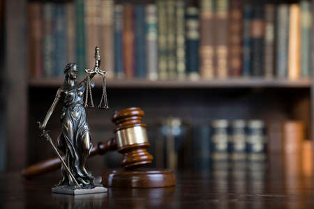 Law theme. Judge chamber. Themis and gavel on brown shining desk. Collection of legal books in the bookshelf.