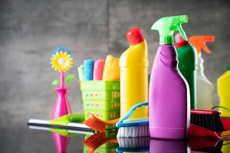 Summer house and office cleaning. Colorful set of bottles with clining liquids and colorful cleaning kit on the gray tiles background.
