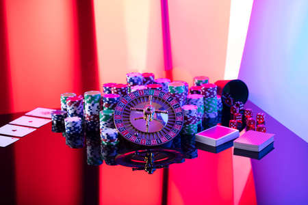 Casino theme.  Roulette wheel, cards, poker chips and dice on red background. 版權商用圖片