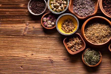 Natural medicine background. Assorted dry herbs in bowls and brass mortar on rustic wooden table. 版權商用圖片